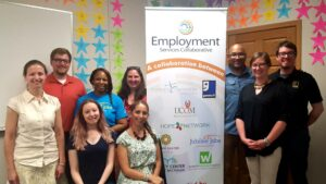 A group of people standing together beside a Disability Advocates employment banner