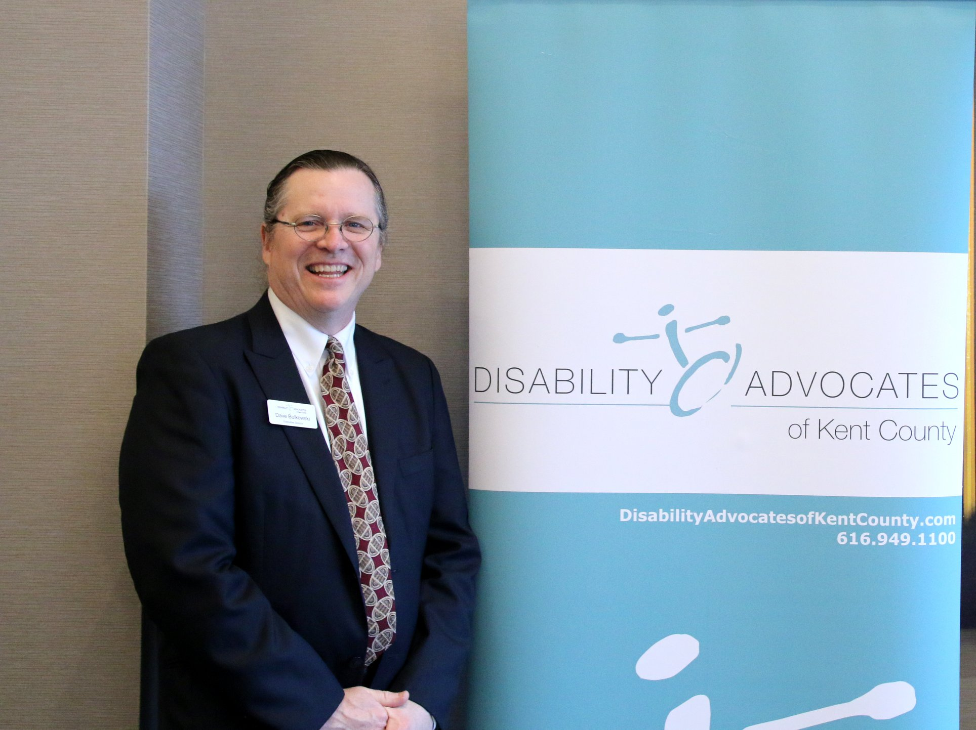 Doug standing next to a Disability Advocates banner