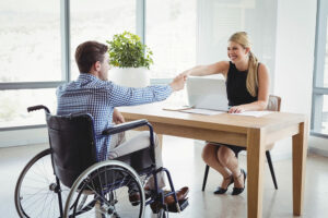 Man in a wheelchair shaking hands with a blonde woman behind a desk