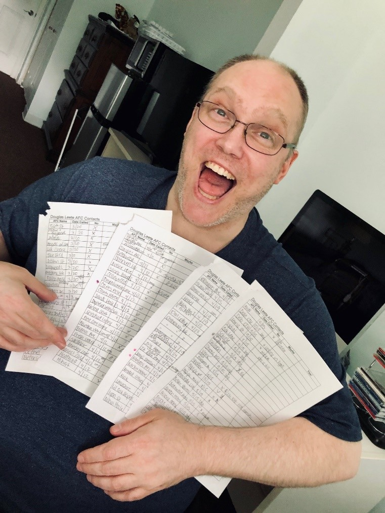 Doug smiling into the camera with a series of sign up sheets