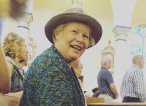 Older woman smiling over her shoulder at the camera