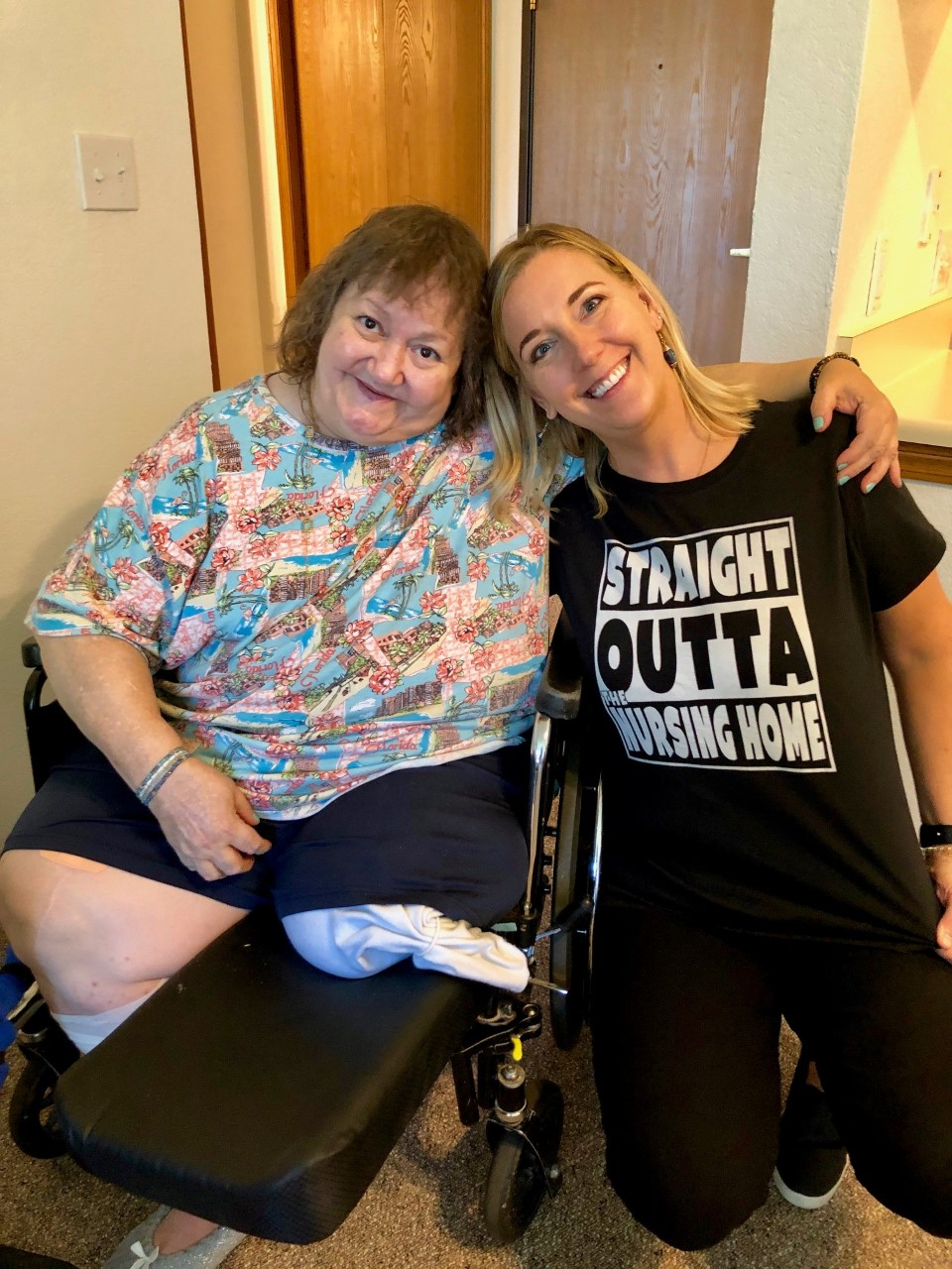 "Young woman leaning towards another woman in a wheelchair wearing a ""straight outta the nursing home"" tee shirt"