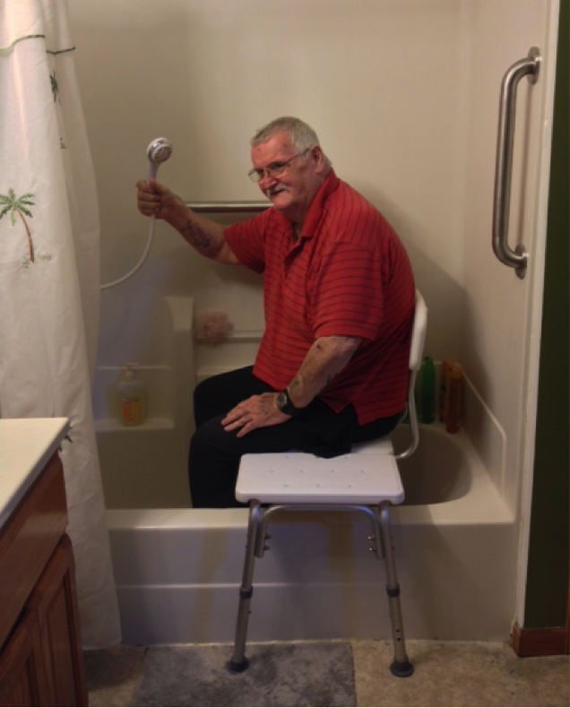 man fully clothed sitting on transfer bench in tub