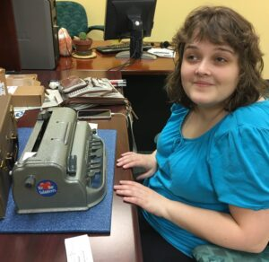 Kristen Kelling seated in front of Braille machine smiling at camera